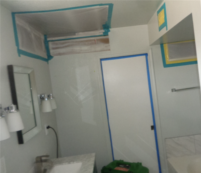 Bathroom with white walls and containment tarp sealing all openings to the room including air vents